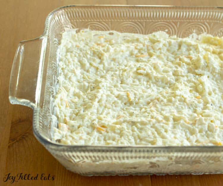 hasbrown casserole spread in a glass baking dish