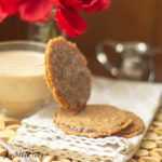 small stack of florentine cookies with one cookie leaning on a glass cup of coffee