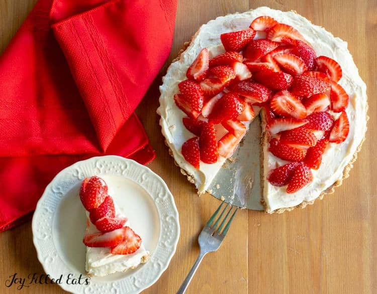 overhead view of strawberry tart with slice missing next to white plate with slice of strawberry tart