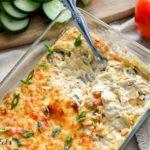 Casserole dish of keto tex-mex Poblano Artichoke Dip with utensil sticking in