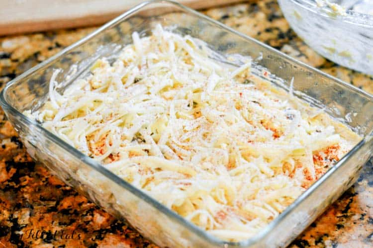 baking dish of keto tex-mex poblano artichoke dip topped with shredded cheese before baking