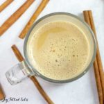 overhead view of Snickerdoodle latte in a glass mug surrounded by cinnamon sticks
