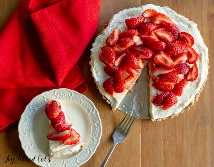 overhead shot of the strawberry tart recipe with a slice on a white plate and a fork and red napkin