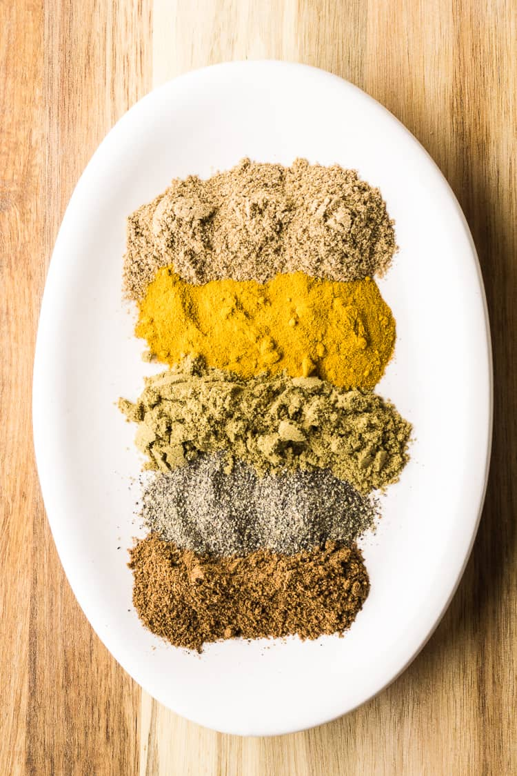 the spices for curry on a white plate