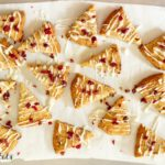 lemon drizzle cranberry cookies arranged on parchment paper from above