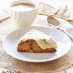 maple oat nut scones with a glaze icing on a plate next to a spoon and cup of coffee