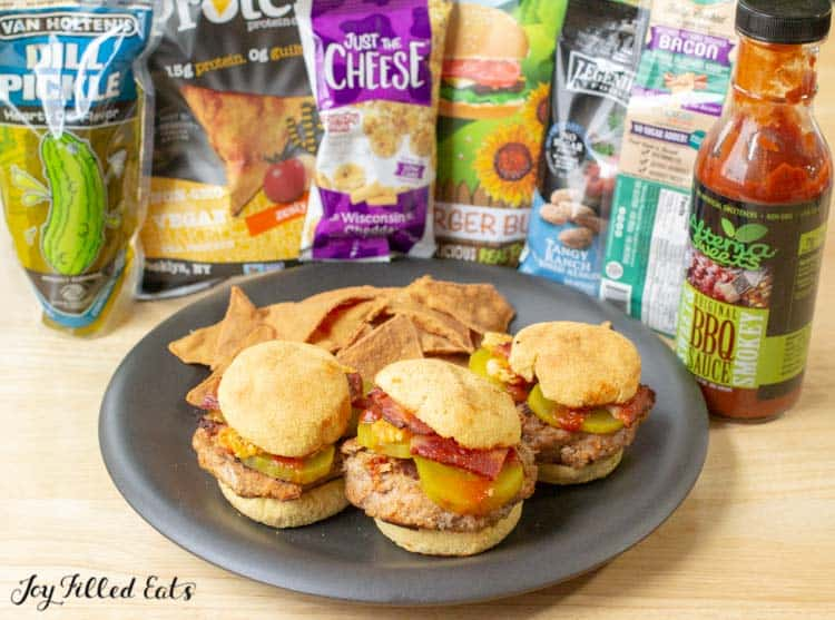 three sliders on a plate with chips in front of packaged ingredients