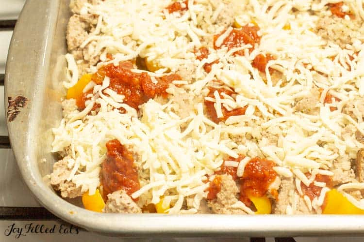 casserole dish of stuffed pepper casserole topped with shredded cheese before baking