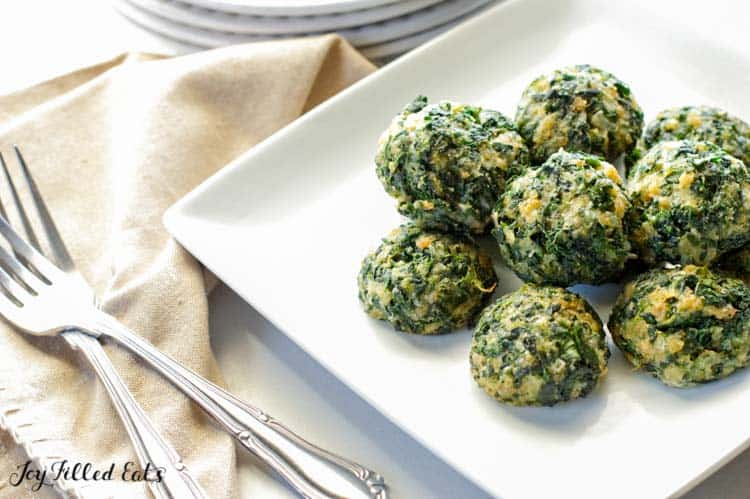 pile of spinach balls on a square white plate on a table with forks