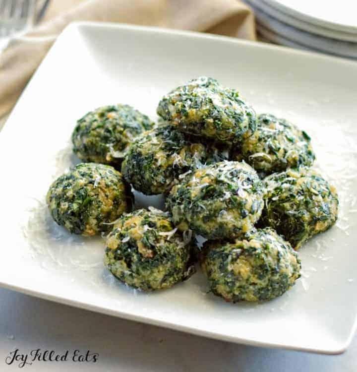 pile of spinach balls with Parmesan on a square white plate
