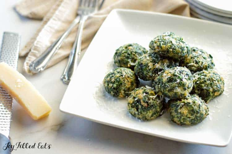 parmesan spinach balls on a white plate with shredded cheese