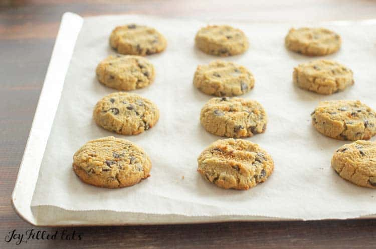 the baked eggless chocolate chip cookies on a parchment lined cookie sheet