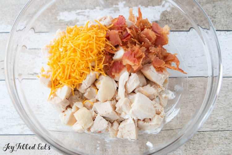 Keto Bacon Ranch Chicken Salad ingredients of Chicken pieces, shredded cheddar cheese and bacon pieces in clear mixing bowl