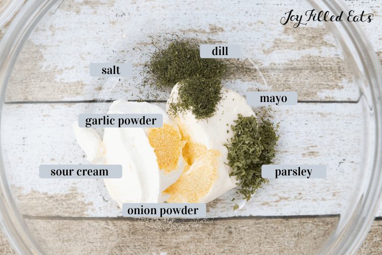 Homemade ranch ingredients in a clear mixing bowl. Includes mayo, sour cream, dill, garlic powder, onion powder, salt and parsley