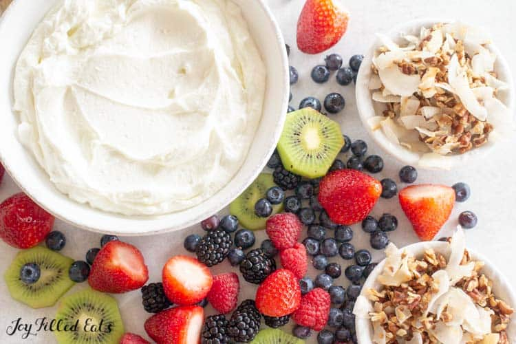 large white bowl of yogurt surrounded by fruit and two small bowls of healthy granola from above
