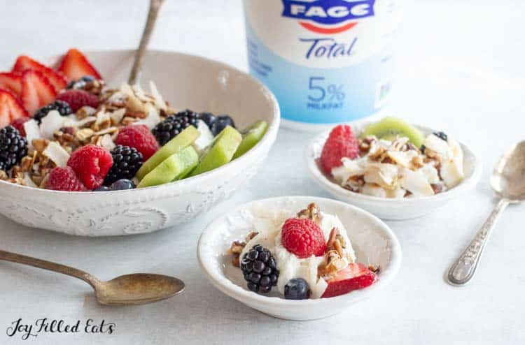 two small bowls of yogurt with fruit and granola topping in front of large bowl of yogurt parfait and Fage Total yogurt container