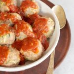 close up of baked turkey meatballs in a bowl covered in marinara sauce place with a spoon