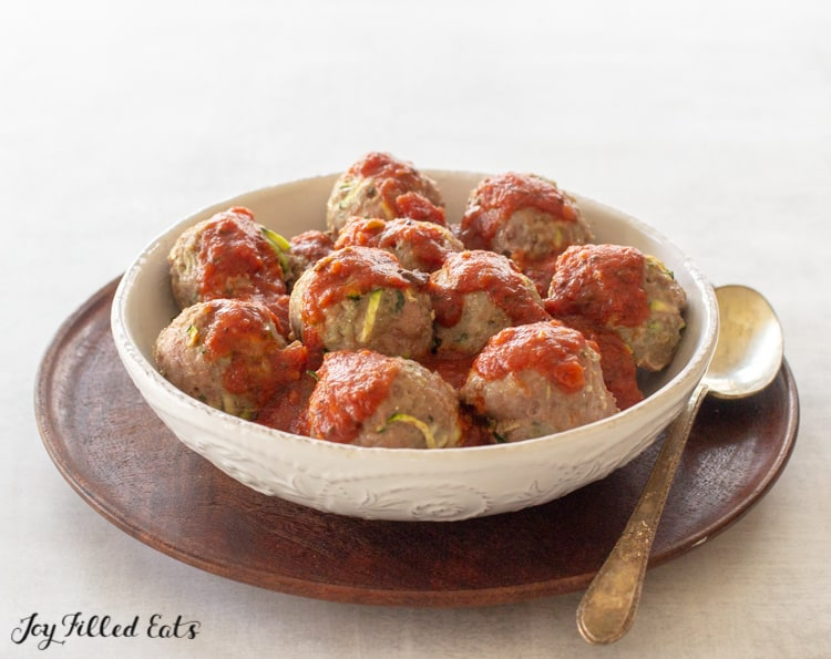 baked turkey meatballs in a bowl covered in marinara sauce place with a spoon
