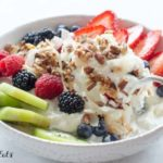 hand holding spoon lifting a bit of yogurt from bowl topped with various fruits and healthy granola