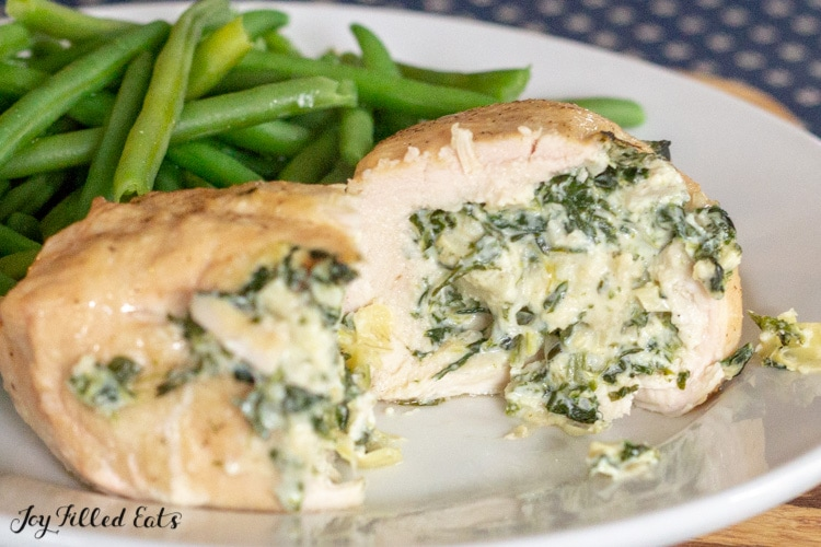 one spinach & artichoke stuffed chicken breast on a white plate sliced in half to show the inside filling