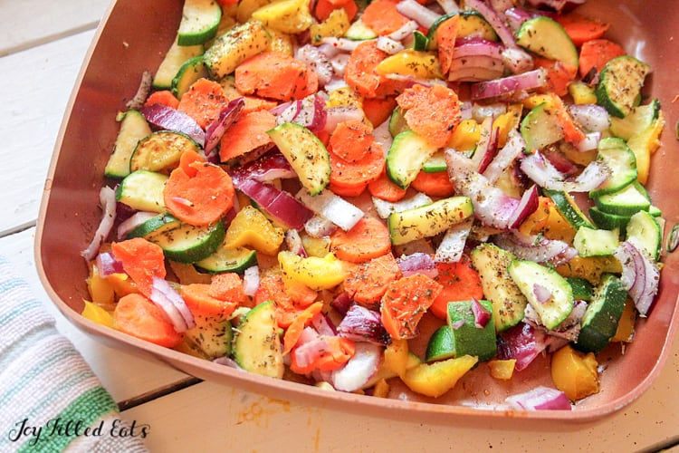 sauteed zucchini carrots onions and peppers in a square copper frying pan