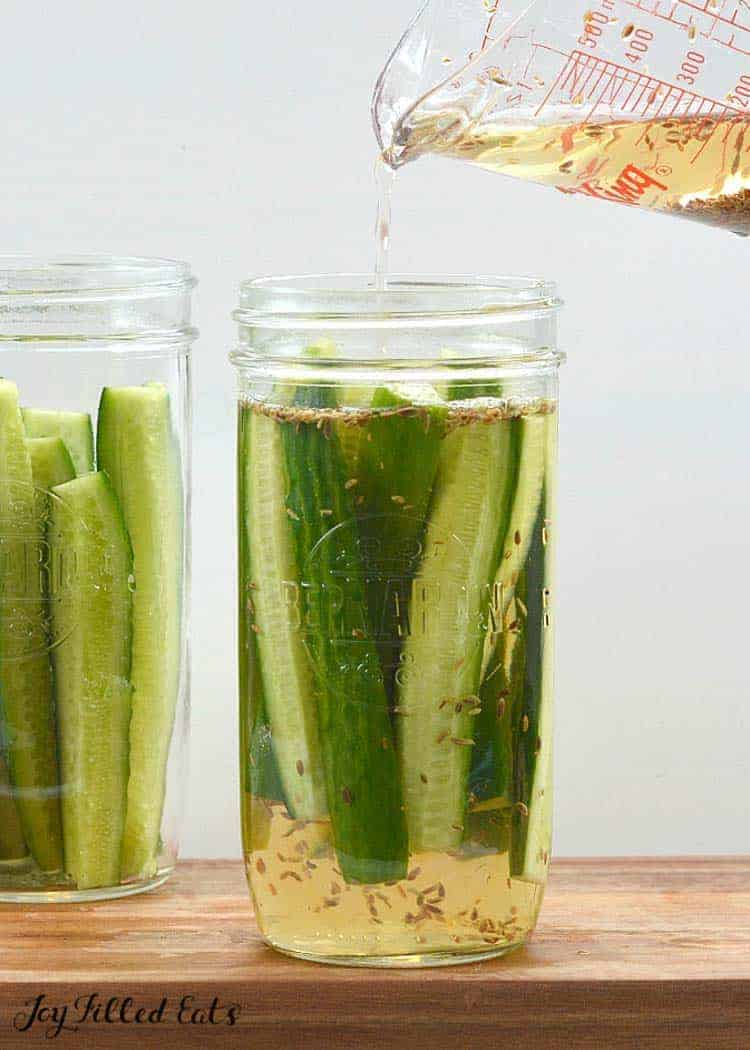 pouring brine over the mini cucumbers in jars