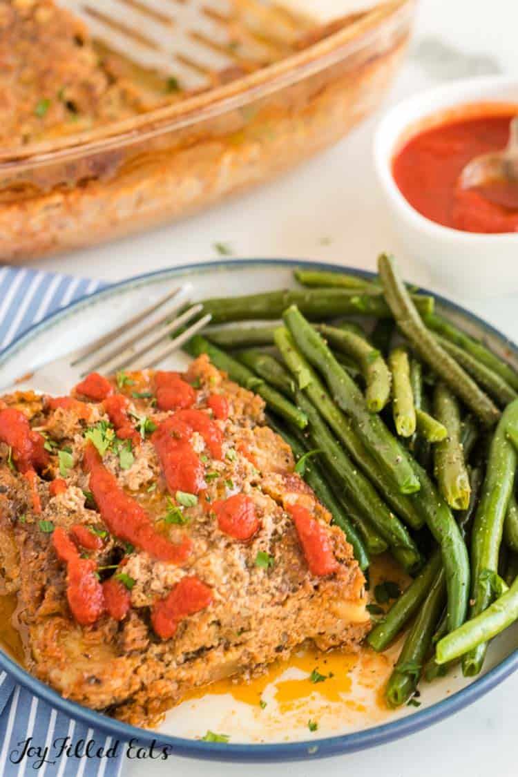 serving of keto turkey meatloaf with a side of green beans on a plate with fork next to jar of marinara sauce and casserole dish of meatloaf