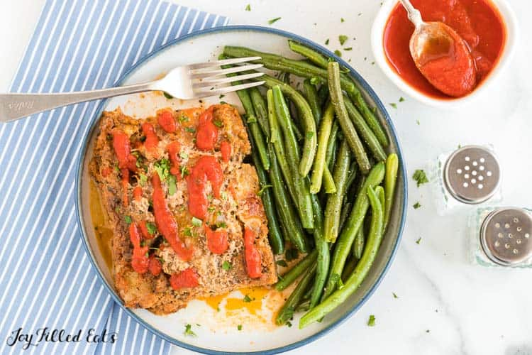 serving of keto turkey meatloaf with a side of green beans on a plate with fork next to jar of marinara sauce from above