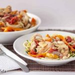 bowl and serving bowl full of slow cooker chicken cacciatore with fork