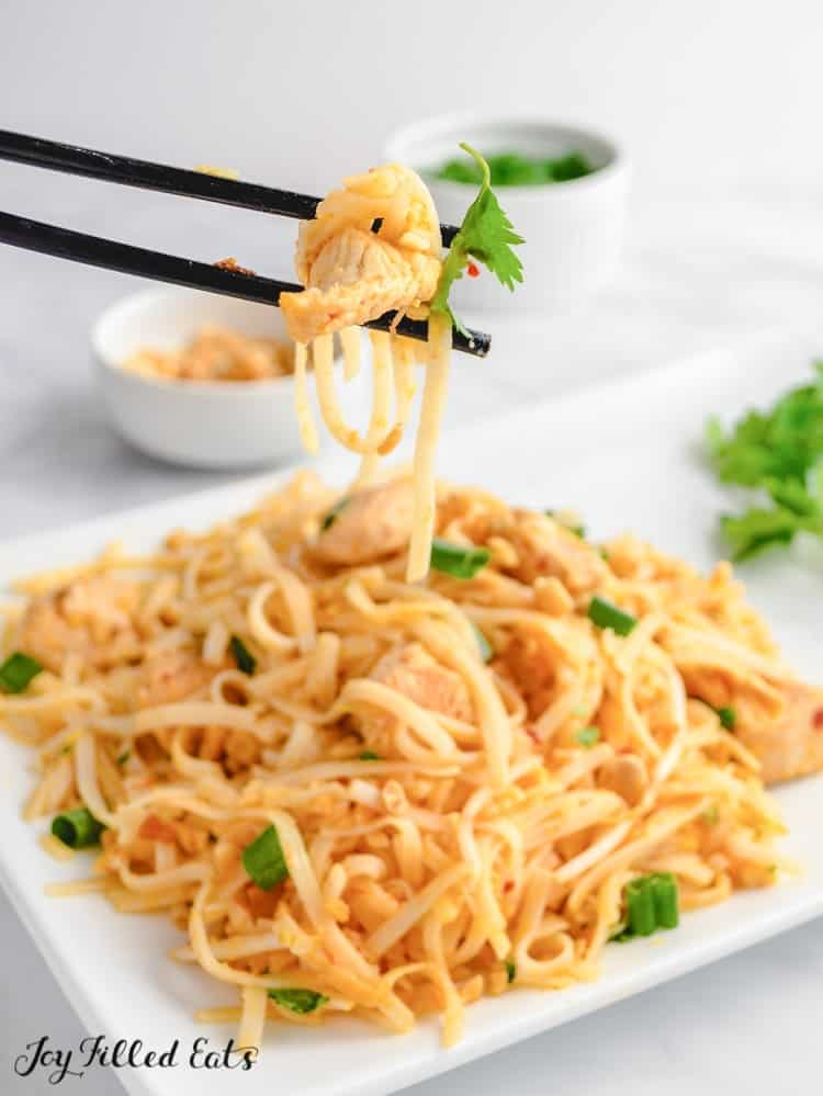 chopsticks holding noodles from plate of keto chicken pad thai