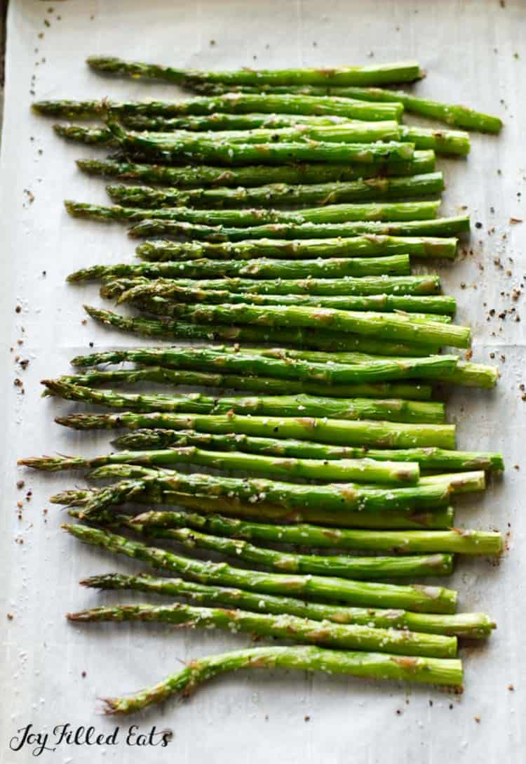 asparagus seasoned and lined on a sheet pan close up