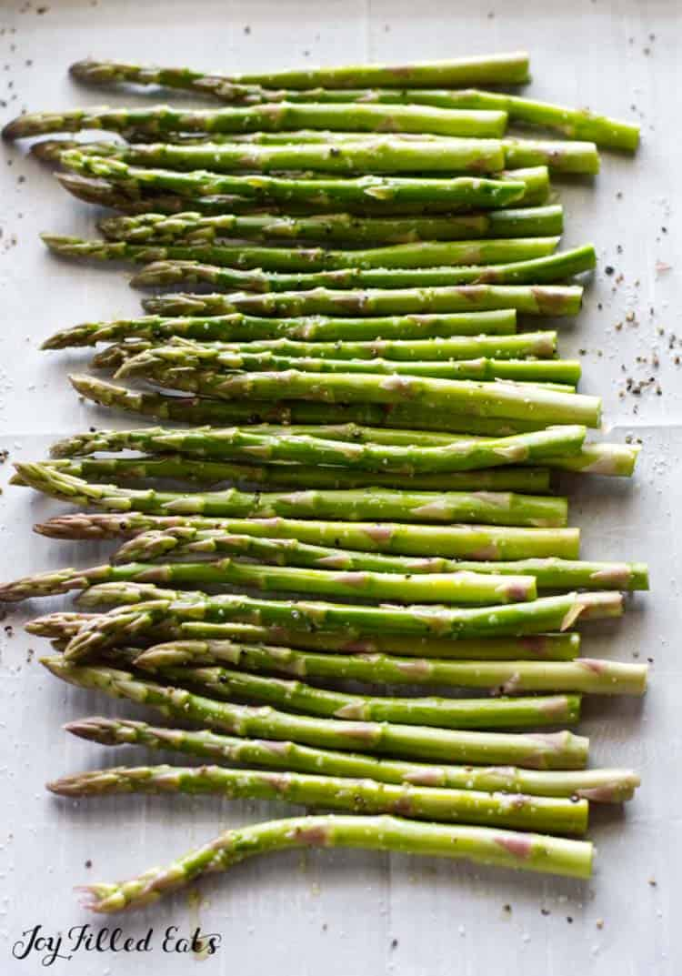 asparagus seasoned and lined on a sheet pan