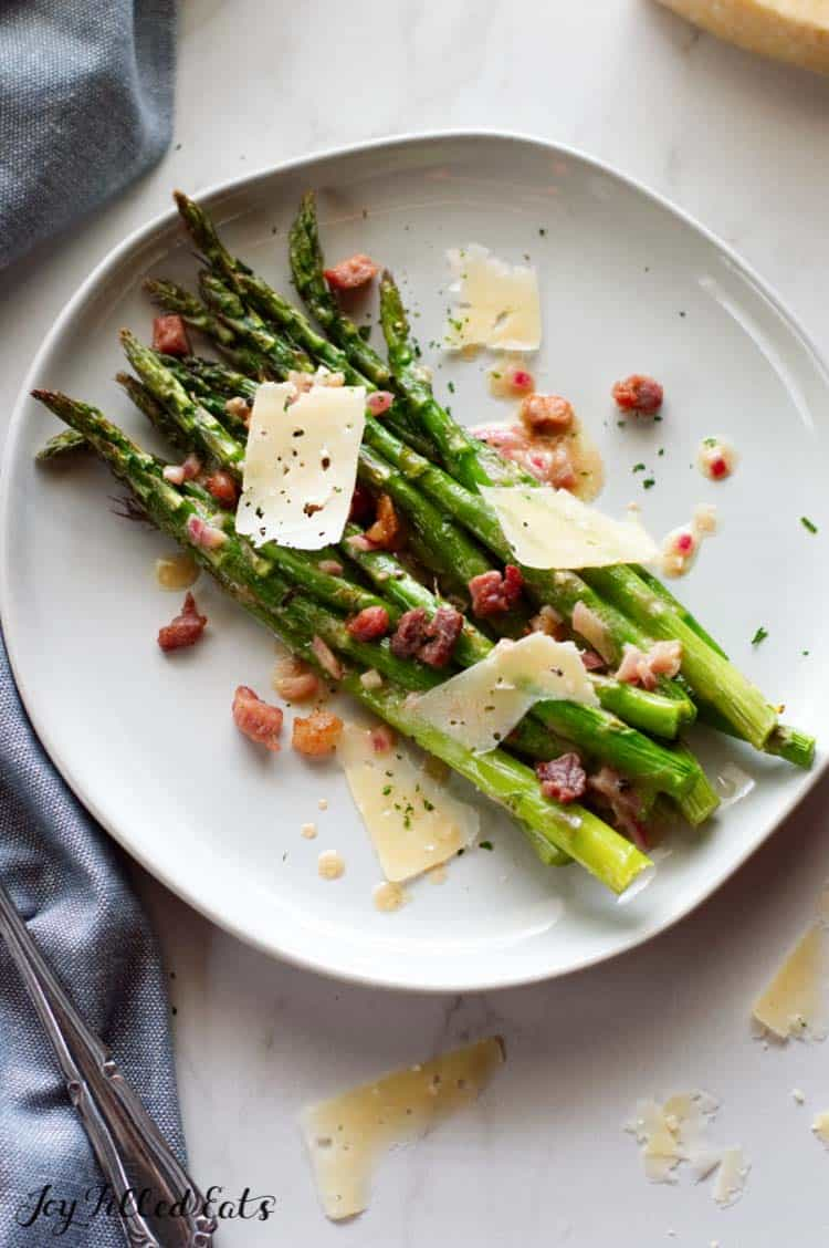 plate of roasted asparagus topped with prosciutto, dijon vinaigrette and cheese shavings