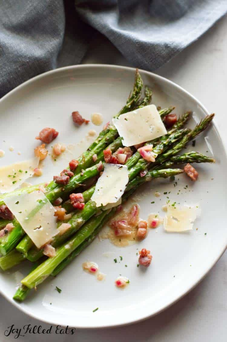 plate of roasted asparagus topped with prosciutto, dijon vinaigrette and cheese shavings close up