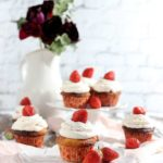 Low carb cupcakes with strawberry whipped cream on different plates with roses in the background.