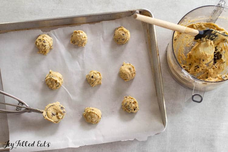 parchment lined sheet pan with cookie dough balls and ice cream scoop next to bowl of almond flour cookie dough batter