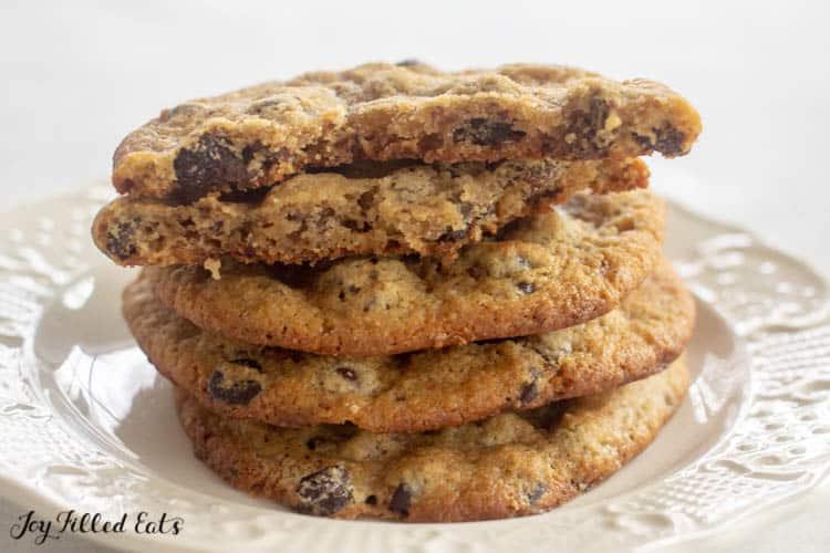 stack of almond flour chocolate chip cookies with top cookie broken in half
