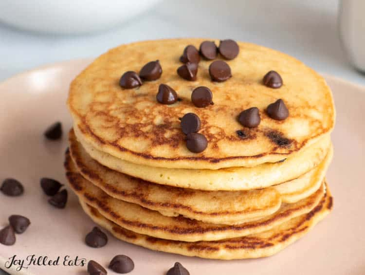 stack of almond flour pancakes topped with chocolate chips on a plate close up