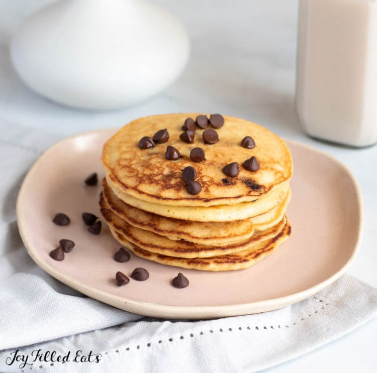 stack of almond flour pancakes topped with chocolate chips on a plate