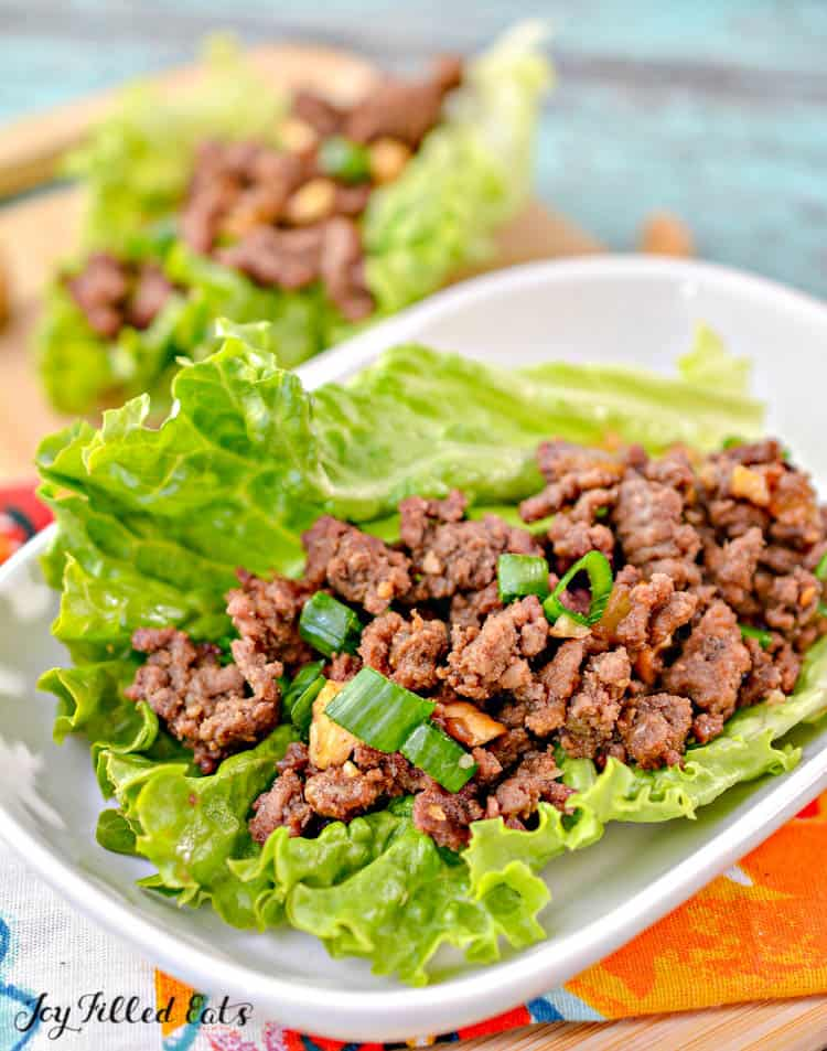 asian lettuce wrap with ground beef placed on a white plate close up