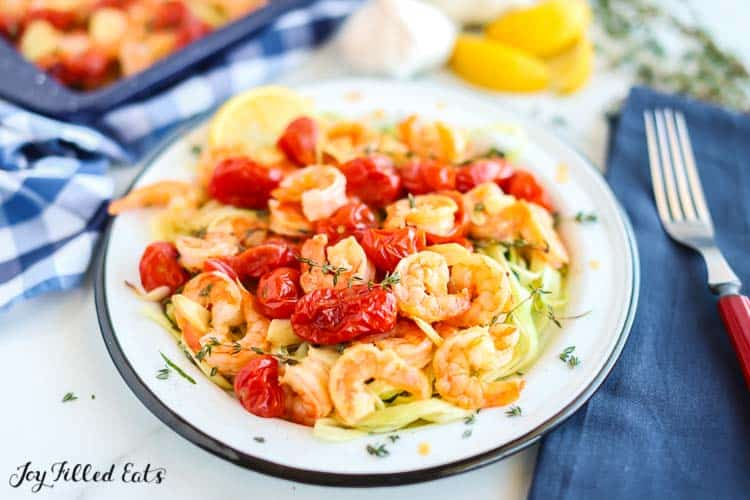baked shrimp and garlic with cherry tomatoes in a bowl next to a fork placed on a blue cloth napkin