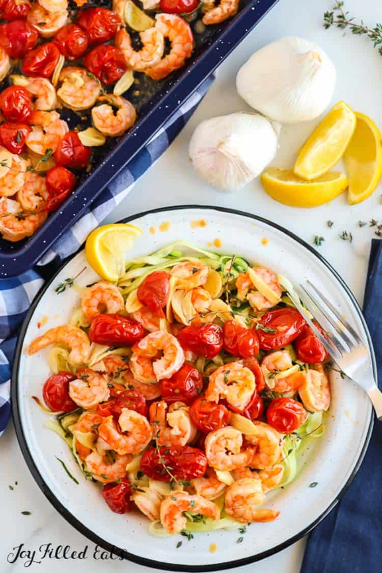 bowl and fork of baked shrimp and garlic with cherry tomatoes next to sheet pan of more baked shrimp, garlic bulb and lemon wedges