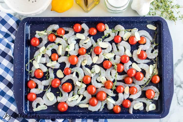 a sheet pan with raw shrimp, sliced garlic, tomatoes, and thyme