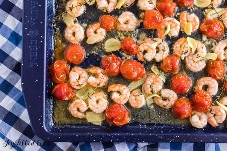 Shrimp, garlic and cherry tomatoes on a sheet pan from above