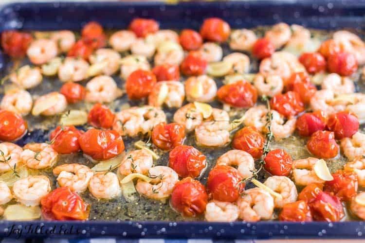 Shrimp, garlic and cherry tomatoes baking on a sheet pan