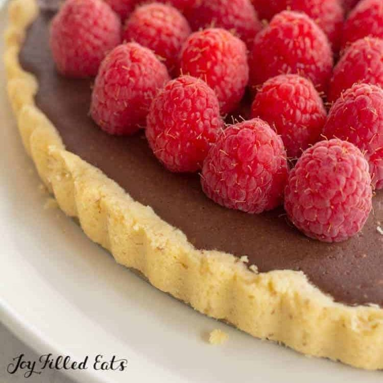 keto chocolate tart topped with raspberries close up