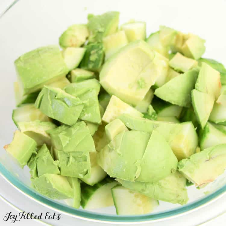 close up of mixing bowl filled with diced avocado and cucumber