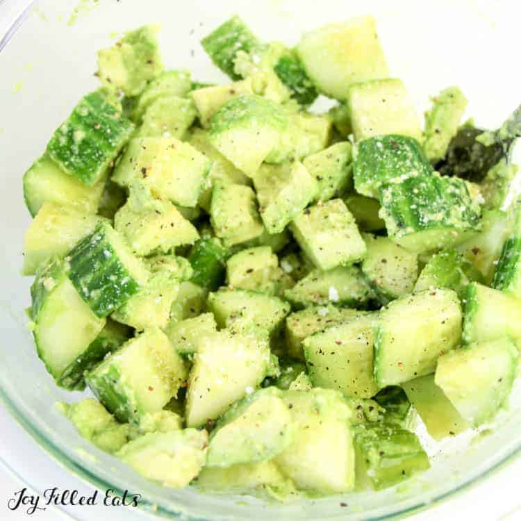 diced cucumber and avocado seasoned in a mixing bowl