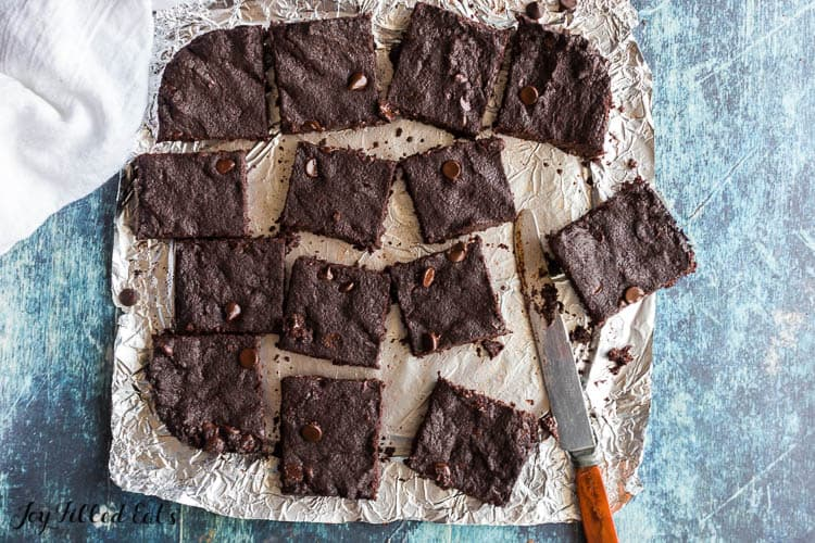 flourless fudge brownies cut into squares scattered on aluminum foil with knife