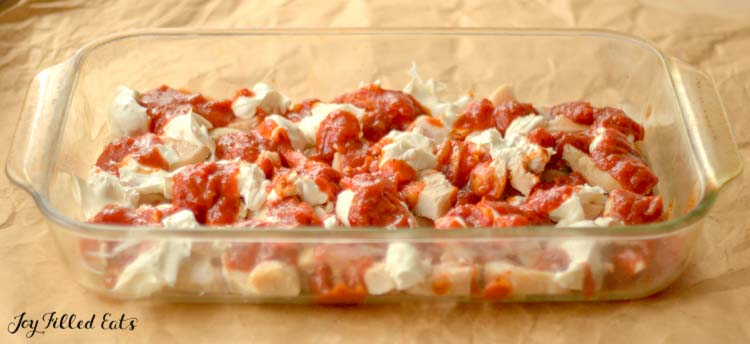 casserole dish layered in chicken pieces and marinara sauce